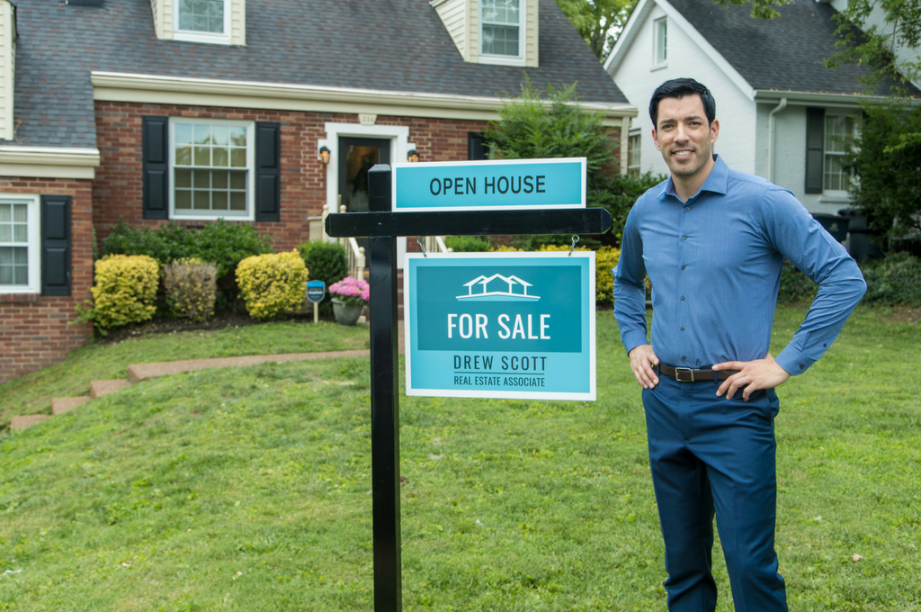 Drew Scott standing in front of a For Sale sign at a home
