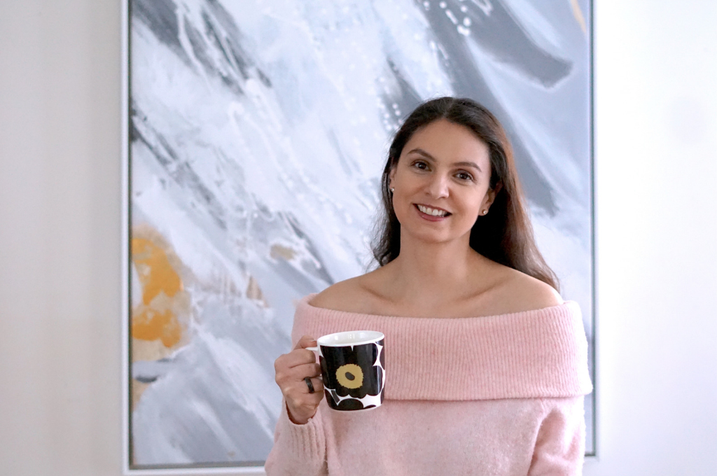 Lucila Diaz of Harmony Sense in front of art with mug